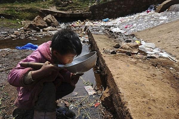 Một cậu bé đang phải uống nước ô nhiễm từ một con sông ở tỉnh Vân Nam, Trung Quốc